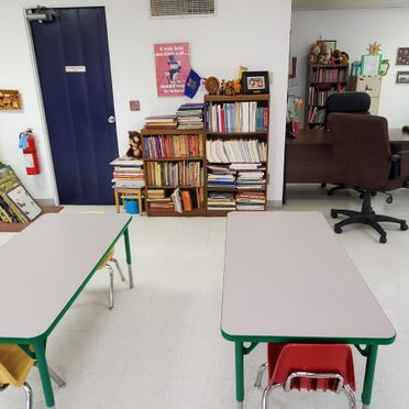 classroom with books, table, and chairs